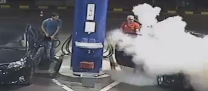 Tankwart löscht Zigarette von Raucher mit einem Feuerlöscher